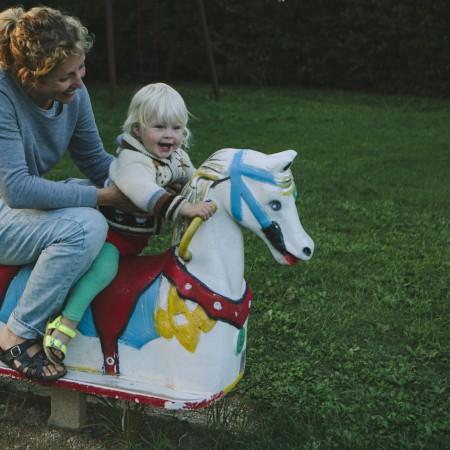 Femke met dochter Lena op een hobbelpaard